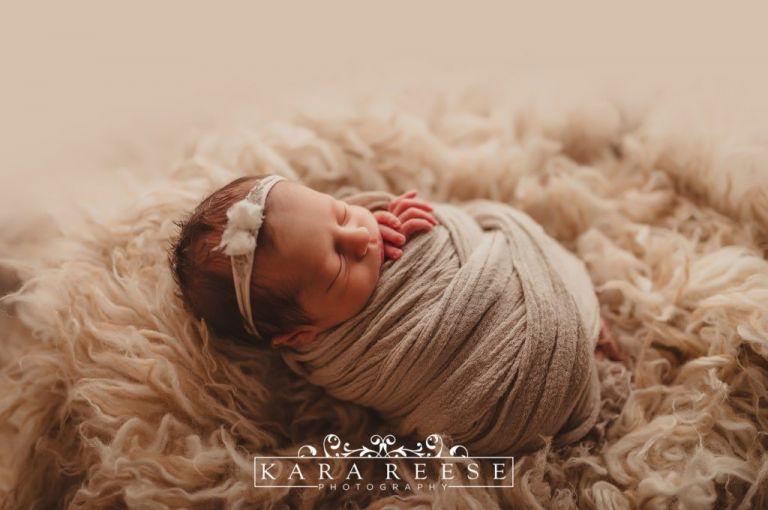 baby girl sleeping in tan with sheep rug