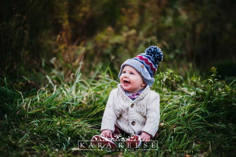 baby boy in winter hat sitting in grass smiling